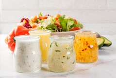 Classic salad dressings. Set of classic salad dressings - honey mustard, ranch, vinaigrette, lemon & olive oil,  on white marble table, copy space Royalty Free Stock Photography