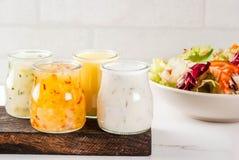 Classic salad dressings. Set of classic salad dressings - honey mustard, ranch, vinaigrette, lemon & olive oil,  on white marble table, copy space Stock Photos