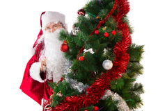 Classic Santa Claus in red costume standing behind Christmas tre Stock Images