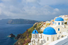 Classic Santorini scene with famous blue dome churches Royalty Free Stock Images