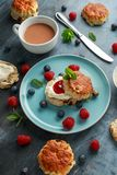 Classic scones with clotted cream, strawberries jam, english Tea and other fruit stock image