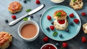 Classic scones with clotted cream, strawberries jam, english Tea and other fruit royalty free stock photos