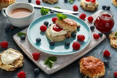 Classic scones with clotted cream, strawberries jam, english Tea and other fruit stock photos