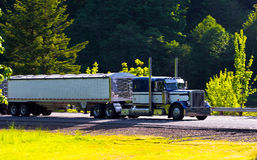 Classic semi truck big rig with two trailers on highway Royalty Free Stock Image