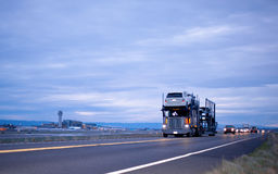 Classic semi truck car hauler stylish in column on night road be. Big rig semi truck with a trailer for transportation vehicles with cars in several levels on Royalty Free Stock Photos