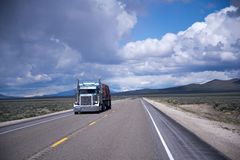 Classic semi truck flat bed with cargo on cloudy road Royalty Free Stock Image