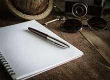 Start The Journey. The Classic Silver Pen on The Blank White Notebook Paper with Antique Key, Sunglasses, Vintage Camera and The Classic World Globe on Old Royalty Free Stock Photography