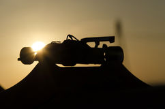 Classic single-seater with sunset in background. Outline of classic single-seater with sunset in background stock image