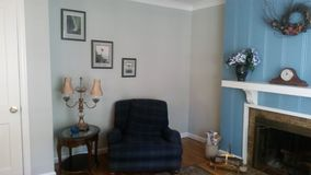 Classic sitting room with blue wall and chair. A classic family room corner. Blue accents and home decor including hanging pictures on the wall, a mantle clock stock photo