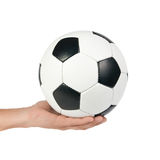 Classic soccer ball at outstretched hand. Royalty Free Stock Photos