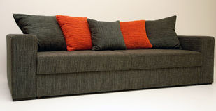 Classic sofa. Modernly designed using straight lines, covered with grey-orange textile on body and pillows, for sitting and sleeping Stock Images