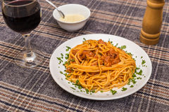 Classic spagetti bolognese. White plate with spagetti bolognese, glass of wine and bowl of parmesan Stock Photography