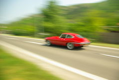 Classic sports car on the road. Classic red sports car driving fast Royalty Free Stock Photo