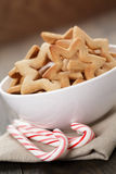Classic star cookies in white bowl with candy cane Royalty Free Stock Images