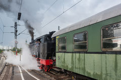 Classic steam locomotive with waggon starting Stock Photography