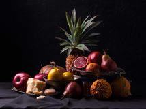 Classic still life with red oranges, apples, pumpkins, pears and pineapple. Stock Photo