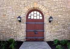 Classic stone building entry. Rustic wood doors fill this stone archway in a classic rustic stone building royalty free stock photography