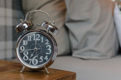 Classic style alarm clock on wooden table in bedroom Royalty Free Stock Photos