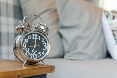 Classic style alarm clock on wooden table in bedroom Royalty Free Stock Photography