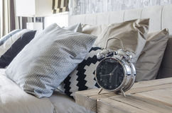 Classic style alarm clock on wooden table in bedroom Stock Photography