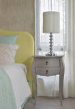 Classic style bedside table with reading lamp next to cozy style bedding. With many style of green and yellow pillows stock photo