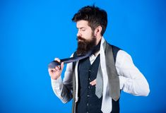 Classic style. How to match necktie with shirt and suit. Man bearded hipster hold few neckties on blue background. Guy. With beard choosing necktie. Gentlemens royalty free stock photography
