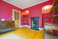 Classic style living room in red. With wooden floor and fireplace royalty free stock images