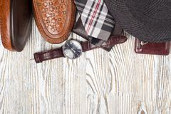 Classic style men`s shoes smartphone watch tie purse camera. On a white wooden background Stock Images