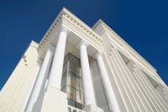 Classic style white building facade detail with pillars against. Clear blue sky. Modern architecture. Low angle view Stock Image