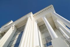 Classic style white building facade detail with pillars against. Clear blue sky. Modern architecture. Low angle view Royalty Free Stock Image