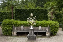 Classic sundial on stone plinth in beautiful formal garden of Twickel Estate, Hof van Twente. Beautiful forged sundial on ornate old stone plinth in the formal stock photo