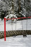 Classic swing set in a public park, red support stand and black rubber baby swing seats, snowy day royalty free stock photo