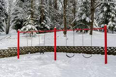 Classic swing set in a public park, red support stand and black rubber regular and baby swing seats, snowy day royalty free stock photography