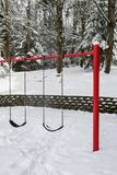 Classic swing set in a public park, red support stand and black rubber swing seats, snowy day royalty free stock photography