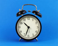 Classic table clock on a blue background. Royalty Free Stock Image
