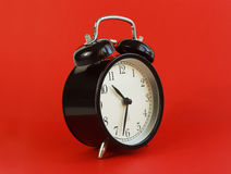 Classic table clock on a red background. Stock Photo
