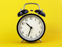 Classic table clock on a yellow background. Stock Photography