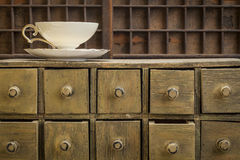 Classic tea cup. On top of rustic apothecary drawer cabinet Royalty Free Stock Photo