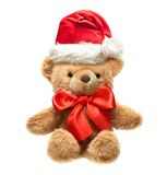 Classic teddy bear with red bow and Santa hat. Royalty Free Stock Images