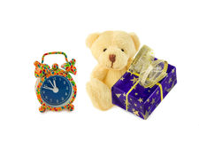 Classic teddy bear sitting with gift and alarm clock on white. Royalty Free Stock Photo