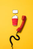 Classic telephone handset and paper cup with speech bubble isolated on yellow Royalty Free Stock Images