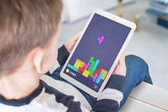 Classic tetris game on tablet in boy hand. View over the shoulder royalty free stock image