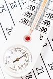 Classic thermometer sitting on a calendar Stock Image