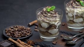 Classic tiramisu dessert with blueberries and strawberries in a glass on stone serving board. On dark concrete background or table stock video footage