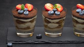 Classic tiramisu dessert with blueberries and strawberries in a glass on stone serving board. On dark concrete background or table stock footage