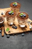 Classic tiramisu dessert in a glass with blueberries on dark concrete background stock image