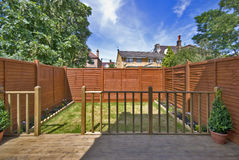 Classic town house courtyard garden renovation. With wooden fence, green and deck terrace Royalty Free Stock Photos