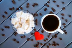 The classic traditional Turkish delight rahat -  oriental delicacy Mug with coffee, roasted grains and red heart. Wooden stock image