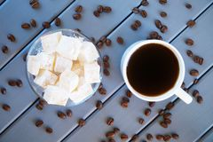 Classic traditional white Turkish delight - Eastern delicacy. Cup with coffee and roasted grains. Wooden background. Daylight royalty free stock photography