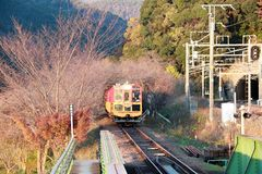The classic train on the Railroad tracks with autumn view. Arashiyama, Kyoto, Japan November 17, 2017: Classic train on autumn at Kameoka Torokko Station It is Stock Photos